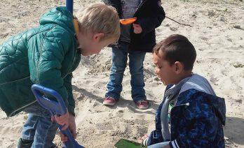 Drie kinderen spelen in het zand